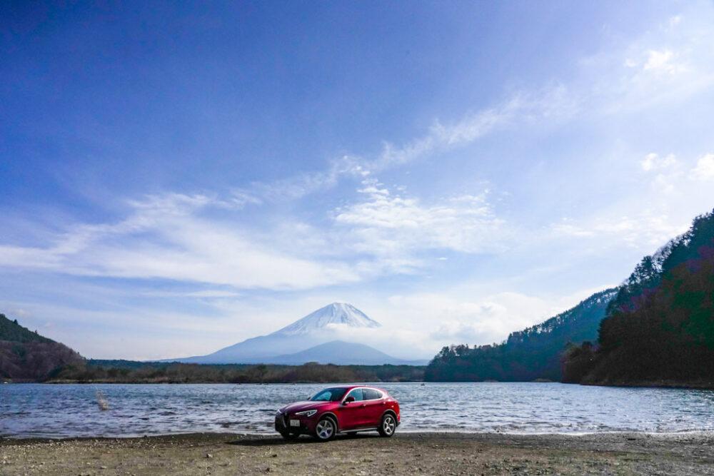 精進湖畔のほとりに停まるアルファロメオ・ステルヴィオ・2.2ターボディーゼル。背景は子抱き富士