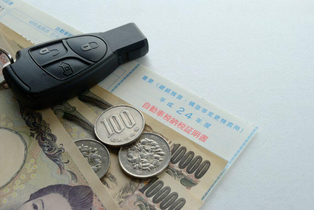 納税証明書の上に置かれた車の鍵とお金