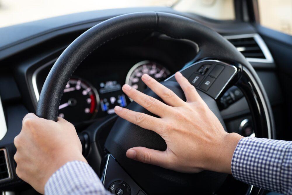 車のクラクションを押す男性の手