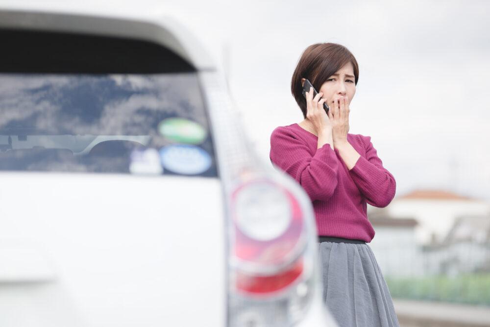 エンジントラブルを起こし電話する女性