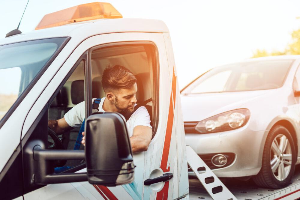 ロードサービスで故障車を牽引する男性