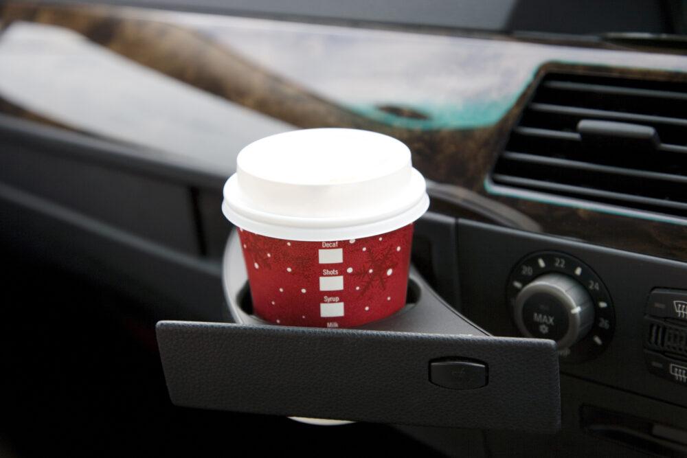 車のドリンクホルダーに入った紙コーヒーカップ