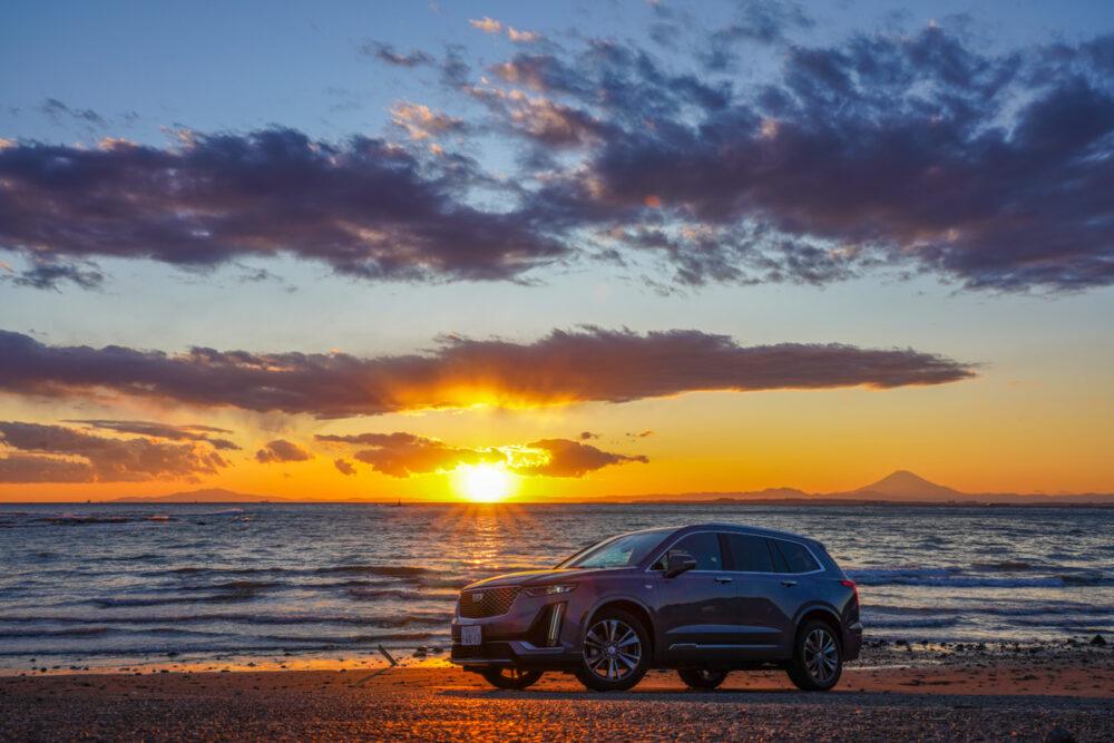 キャデラック XT6 ナイトクルーズ エディション  海に沈む夕日を背景に撮影。遠景に富士山。