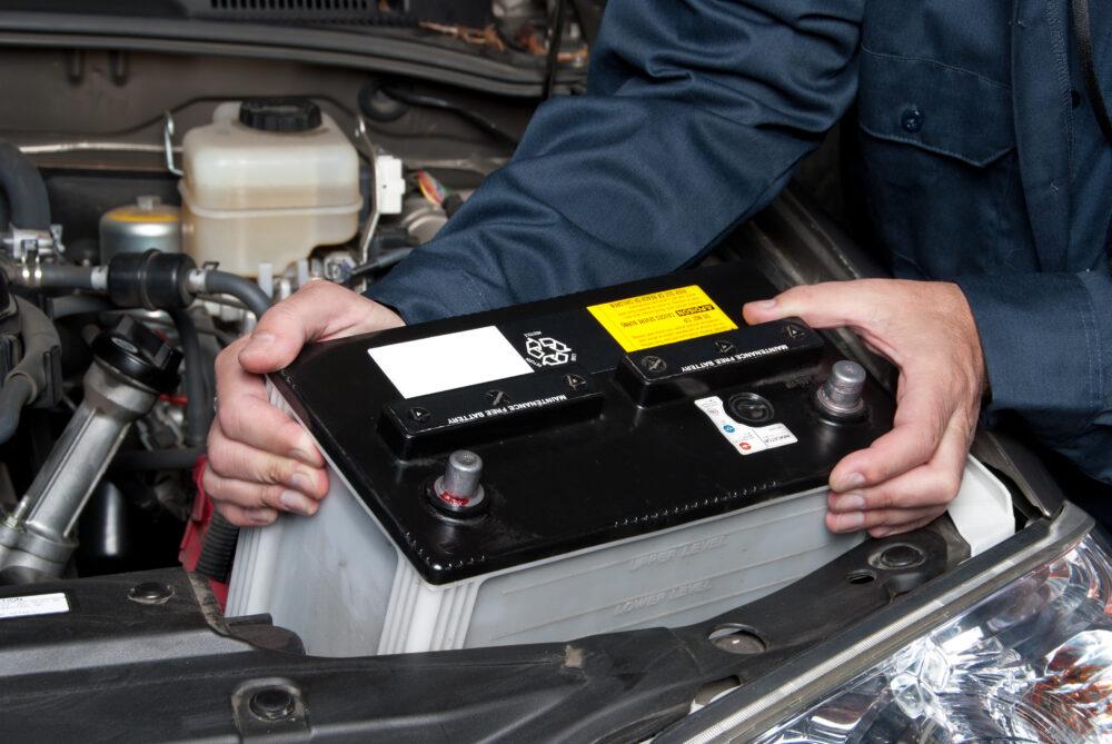 車のバッテリーを交換する整備士