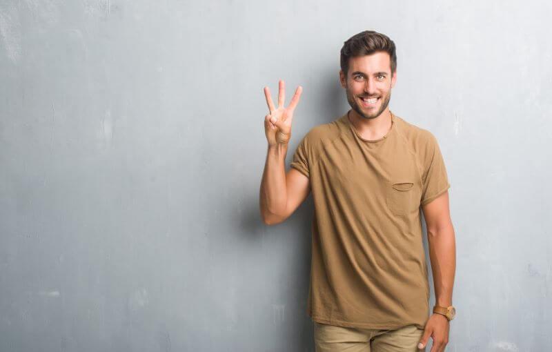 三本指で上を指し笑顔の男性