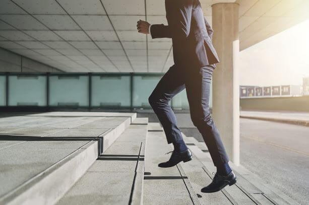 スーツを着た男が階段を駆け上がる姿