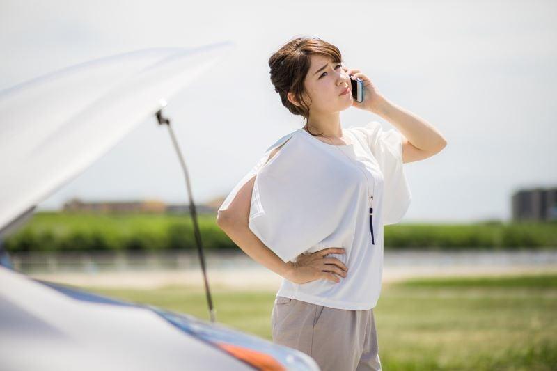 車と電話している女性