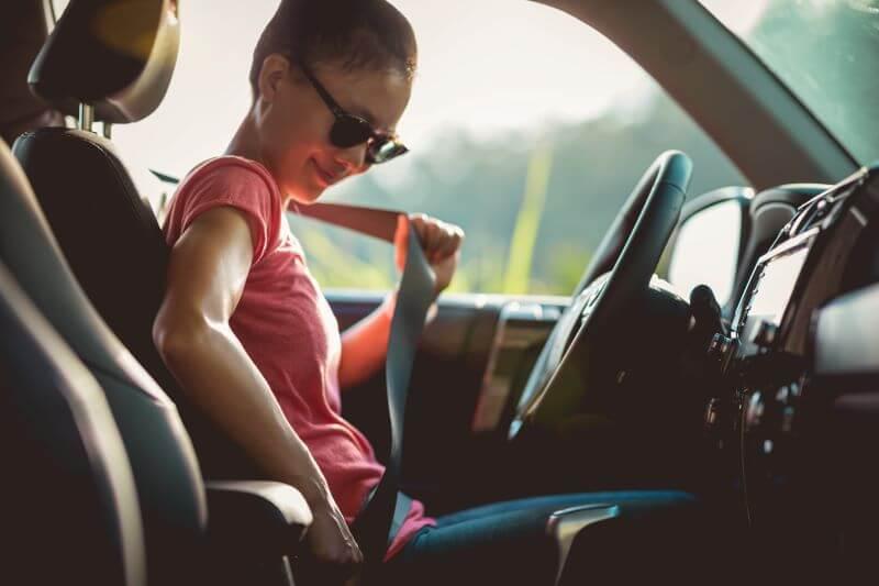シートベルトを装着する女性