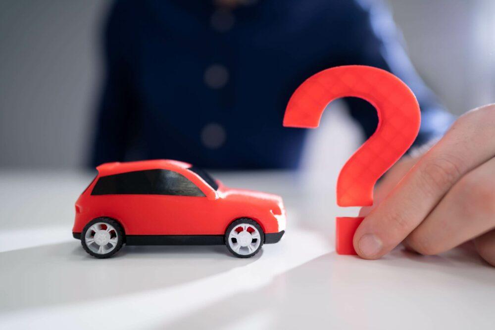 おもちゃの車とクエスチョンマーク