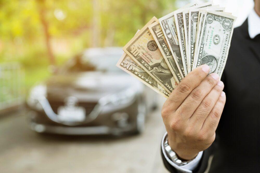 お金を持つ男性と車