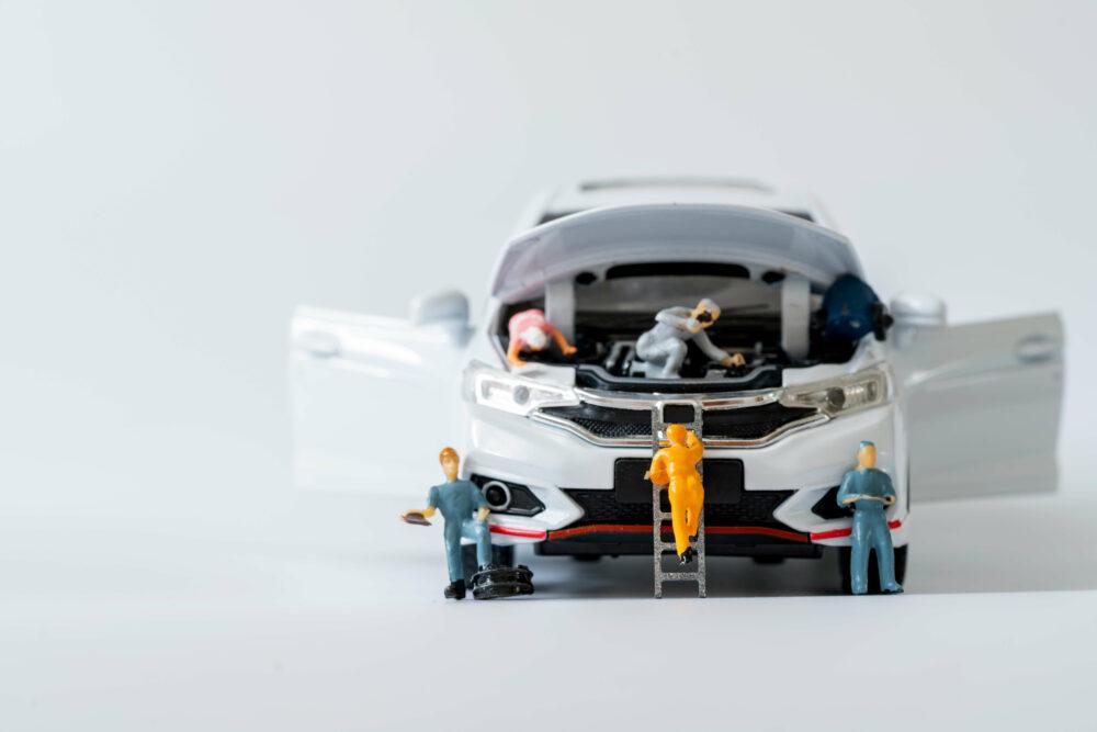 おもちゃの車をメンテナンスする人形