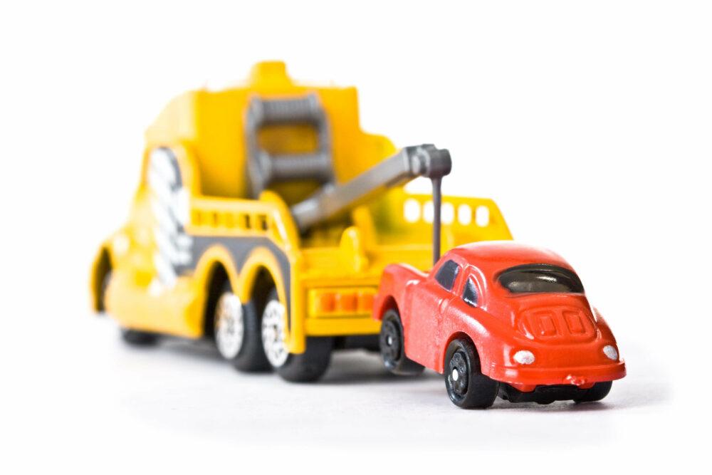 黄色のレッカー車で牽引されている赤い車