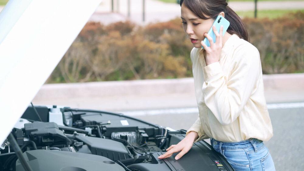 自動車のボンネットを開けて電話する女性