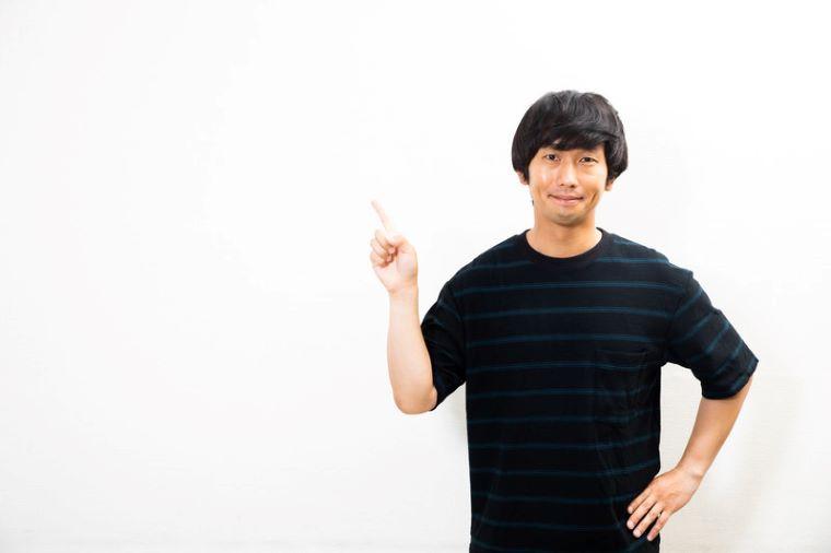 人差し指を立てて上に指す男性