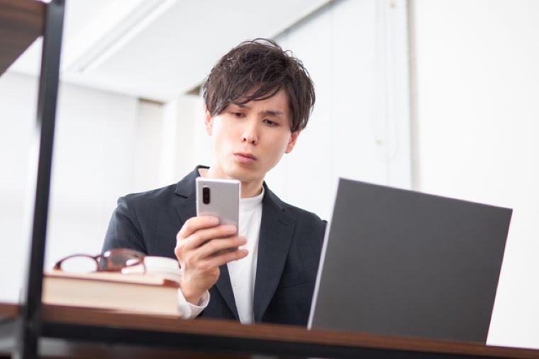 スマホを持ってパソコンを操作する男性