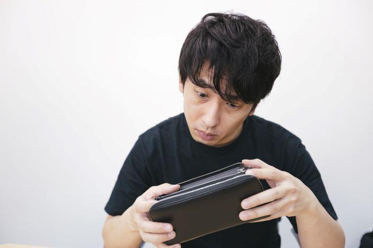 深刻そうな顔で財布を見つめる男性